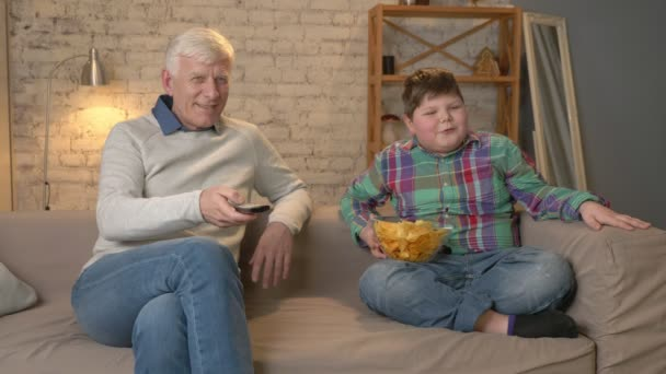 Grandfather and his grandson are sitting on the couch and watching television, eating chips, smiling. An elderly man switches channels, uses a remote control. Home comfort, family idyll, cosiness