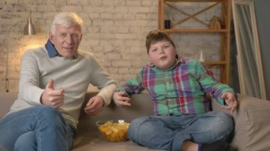 Grandfather and grandson are sitting on the couch watching television, eating chips, rejoicing in victory, fans. Home comfort, family idyll, cosiness concept, difference of generations. 60 fps