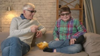 Grandfather is feeding his grandson with chips from his hands. An elderly man and a young fat boy are sitting on the couch in 3d glasses. Home comfort, family idyll, cosiness concept, difference of