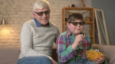 Grandfather and grandson are sitting on the couch and watching a 3D movie in 3d glasses, eating chips, laughing, smiling, comedy, humor, TV, show. Home comfort, family idyll, cosiness concept
