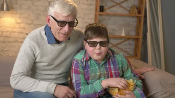 Grandfather and grandson are sitting on the couch and watching a 3D movie in 3d glasses, eating chips, speaking, dancing, TV, show. Home comfort, family idyll, cosiness concept, difference of