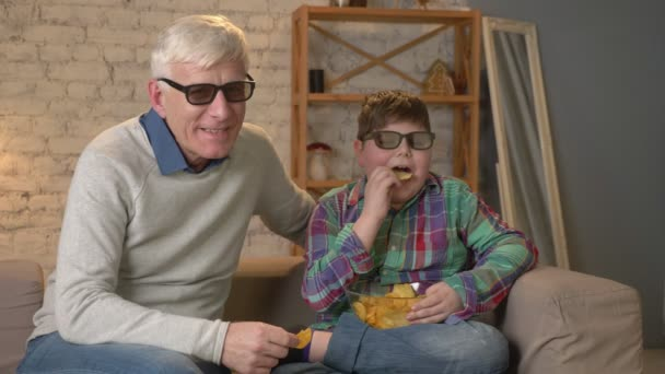 Grandfather and grandson are sitting on the couch and watching a 3D movie in 3d glasses, eating chips, smiling, TV, show. Home comfort, family idyll, cosiness concept, difference of generations 60 fps