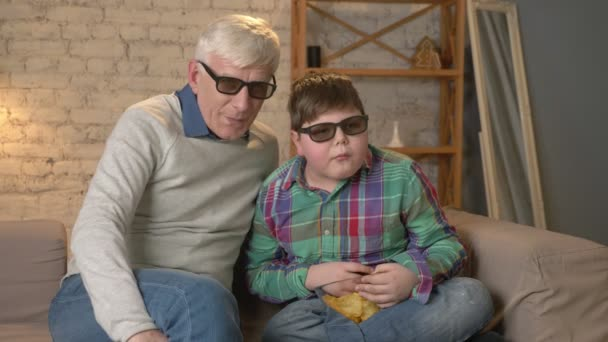 Grandfather and grandson are sitting on the couch and watching a 3D movie in 3d glasses, eating chips, moving, TV, show. Home comfort, family idyll, cosiness concept, difference of generations 60 fps