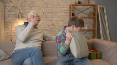 Grandson gives his Grandfather a gift. a fat child gives a gift to An elderly man, Joy, surprise, happiness, emotion, feeling, impulsively, present. Home comfort, family idyll, cosiness concept