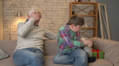 Grandson gives his Grandfather a gift. a fat child gives a gift to An elderly man, Joy, surprise, happiness, emotion, feeling, impulsively, present, hug. Home comfort, family idyll, cosiness concept