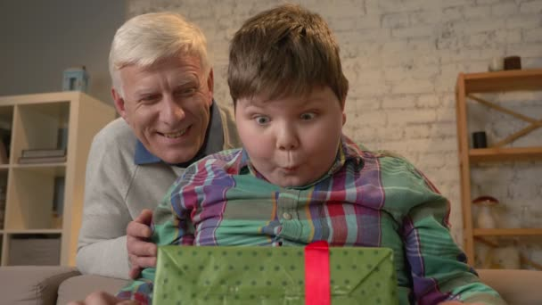 Grandfather gives his grandson a gift. An elderly man gives a gift to a fat child. Joy, surprise, happiness, emotion, feeling, impulsively, present. Home comfort, family idyll, cosiness concept