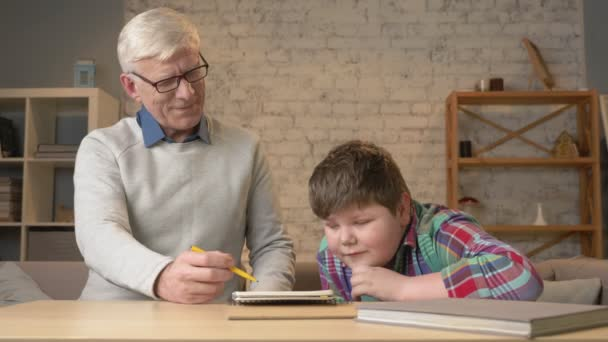 Grandpa helps a grandson with homework. Elderly man helps a young fat child to do homework. Home comfort, family idyll, cosiness concept, difference of generations, close up. 60 fps