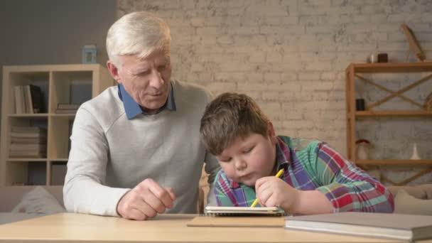 Opa hilft einem Enkel bei den Hausaufgaben. Ein älterer Mann hilft einem kleinen dicken Kind bei den Hausaufgaben. Wohnkomfort, Familienidylle, Gemütlichkeitskonzept, Generationenunterschied, hautnah. 60 fps