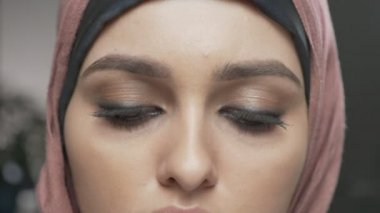 Young beautiful girl in pink hijab looking at camera. Portrait, close-up of eyes 60 fps