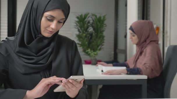 junges hübsches Mädchen in schwarzem Hijab mit Headset, das einem Callcenter antwortet. Araberinnen im Büro. 60 fps