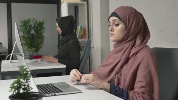 Young beautiful girl in pink hijab puts on glasses and starts working on the computer. Arab women in the office 60 fps