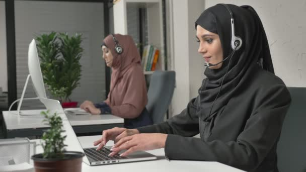 A young beautiful girl in a black hijab is talking on the headset, answering calls in call center. Arab women in the office. 60 fps