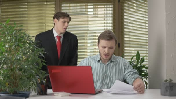 A young subordinate employee brought the boss a report, a document. Makes funny faces while the boss does not see, behind his back. Work in the office. 60 fps