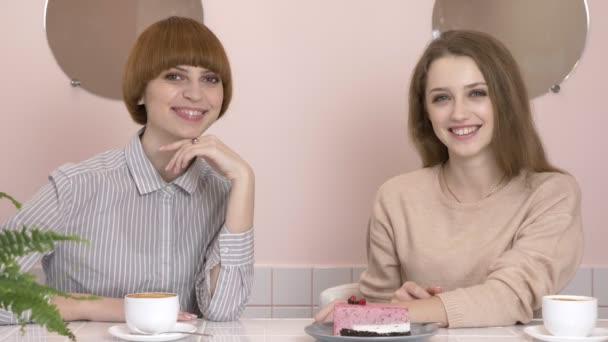 Dvě mladé kavkazský dívky sedí v kavárně a usmíval se, při pohledu na fotoaparát, portrét. Dívky v café konceptu. 60 snímků za sekundu