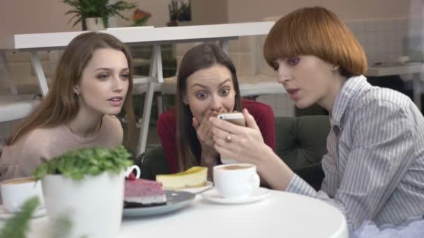 Három fiatal kaukázusi lány ül egy kávézóban, nevetve, mosolyogva, meg, társaság, pletykák, párbeszéd, vita. A café koncepció barátnője. Egy okostelefon segítségével egy videót, vicces, egy fénykép
