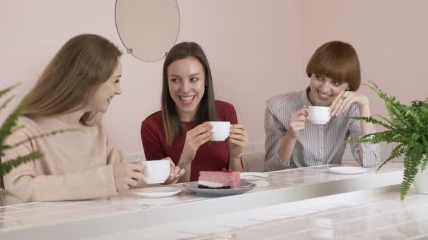 Tři mladé kavkazský dívky sedí v kavárně, pití kávy, jíst dort, usměvavý, smích, gestikuloval rukama, drby starých kamarádek v café konceptu. 60 snímků za sekundu