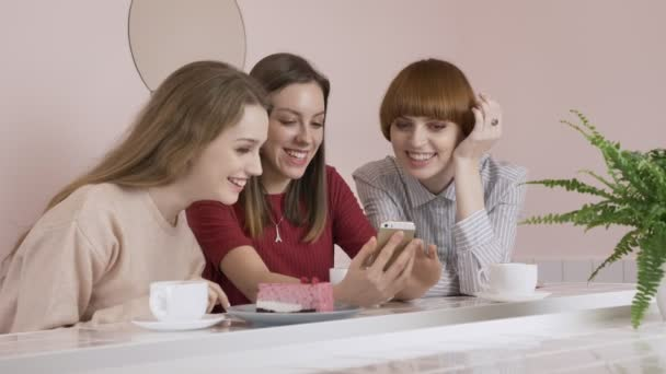 Three young Caucasian girls sitting in a cafe, drinking coffee, eating cake, smiling, laughing, gesturing with their hands, using smartphone, watching funny pictures, videosgossip old girlfriends in a