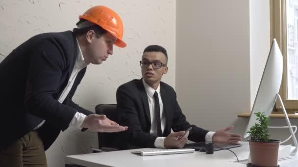 Dvě mladý podnikatel, architekt, diskutovat o projektu a podívejte se na monitor v úřadu. Stavitelé, inženýři, koncept. 60 snímků za sekundu