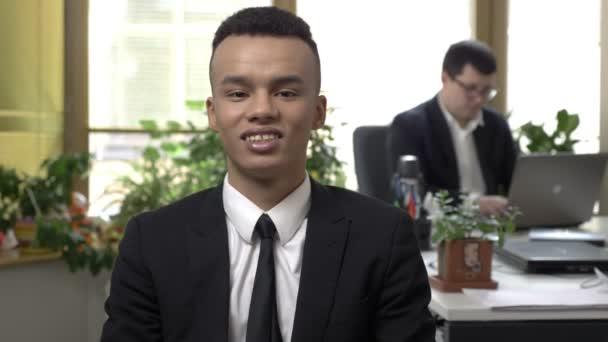 Mladí africké úspěšný podnikatel při pohledu do kamery a usmíval se, muži, kteří pracují na počítači na pozadí. 60 snímků za sekundu
