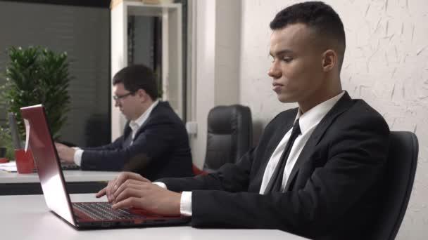 Mladí africké úspěšný podnikatel sedí v kanceláři a pracují na notebooku, kavkazské muži v obleku v pozadí. 60 snímků za sekundu