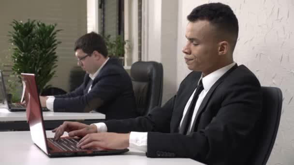 Mladý úspěšný afrických mužů podnikatel pracuje v kanceláři v přenosném počítači, unavená, zavře laptop a masáže svou whisky. Kavkazská muž v obleku v pozadí. 60 snímků za sekundu