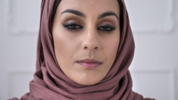 Junge schöne schwere indische Mädchen mit piercing in der Nase Rosa Hijab Blick in die Kamera. Porträt, Baum, weißer Hintergrund, nah oben 60 fps