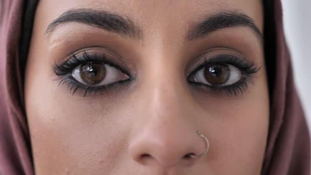 Detail samice indické smutnýma očima. Mladé krásné vážné indická dívka v růžové hidžáb při pohledu na fotoaparát. Portrét, bílým pozadím, zblízka 60 fps