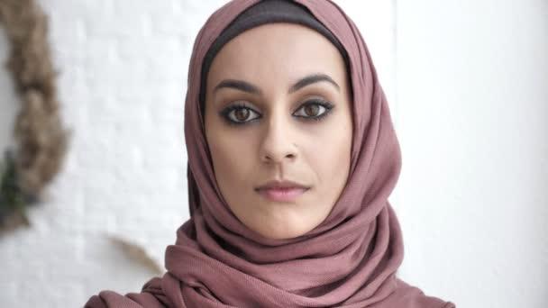 Junge schöne schwere indische Mädchen in Rosa Hijab Blick in die Kamera. Porträt, Baum, weißer Hintergrund, nah oben 60 fps