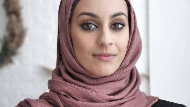 Junge schöne indische Mädchen mit piercing in der Nase Rosa Hijab lächelnd und Blick in die Kamera. Porträt, Baum, weißer Hintergrund, nah oben 60 fps