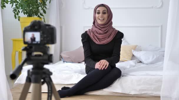 junge schöne indische Mädchen im Hijab Blogger spricht vor der Kamera, gestikuliert, weißes Zimmer, zu Hause Komfort im Hintergrund. 50 fps