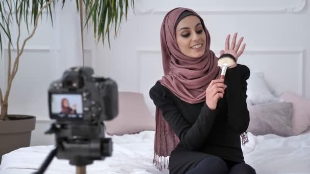 junge schöne indische Mädchen im Hijab Blogger spricht vor der Kamera, lächelt, spricht in die Kamera, zeigt einen Neukauf, Make-up-Pinsel, Make-up-Konzept, Wohnkomfort im Hintergrund. 60 fps