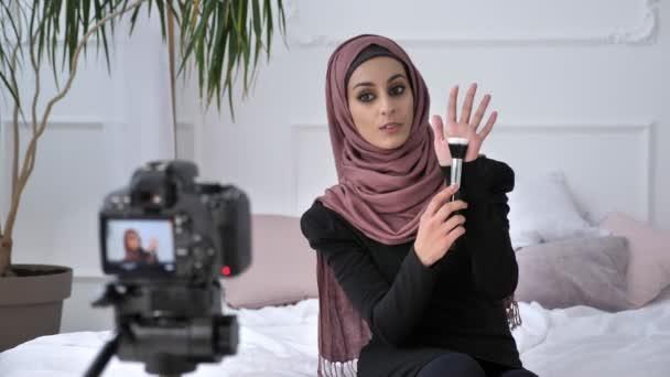 Junge schöne indische Mädchen in Hijab Blogger sprechen vor der Kamera, lächelnd in die Kamera sprechen, zeigt ein Neukauf, Make-up Pinsel, Make-up-Konzept, Wohnkomfort im Hintergrund. 60fps