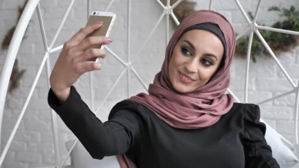 Junge schöne indische Mädchen tragen Hijab, lächelnd, tun Selfie, schwenkten ihre Hand Gruß Geste, auf Wiedersehen 50 fps