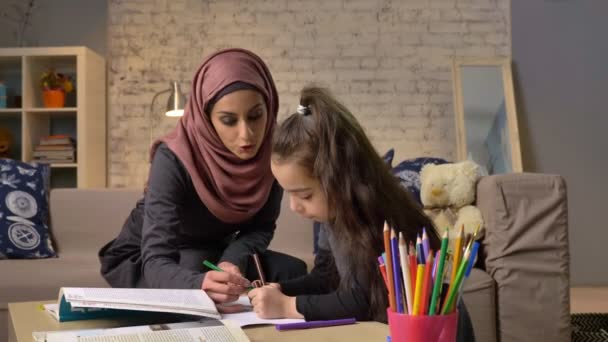 Krásná mladá matka v hidžábu dělá domácí úkoly lekce, malá dcera si vybírá barevné tužky, kreslí, dětské omalovánky, domácí pohodlí v pozadí, barevné tužky 50 fps