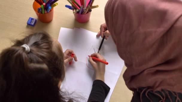 Krásná maminka v hidžábu, malou dcerou barvy s barevné tužky, barvy, dětské omalovánky, koncept rodinné idyly, zblizka, horní snímek 50 fps
