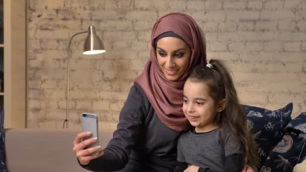 Young beautiful mother in hijab with little girl on couch, smiling, uses smartphone, makes selfie, cuddling, little girl with teddy bear, happy family concept home comfort in the background 50 fps
