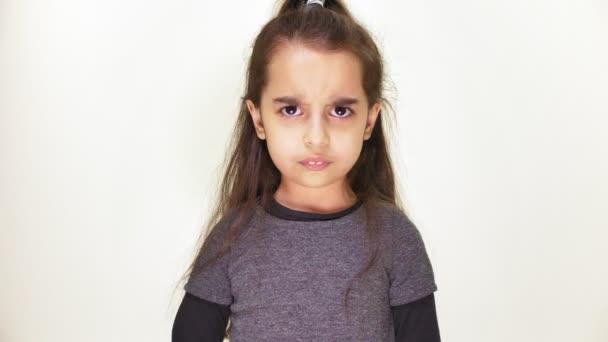 kleines süßes kaukasisches Mädchen, das in die Kamera blickt, wütend und lächelnd, Porträt, weißer Hintergrund 50 fps