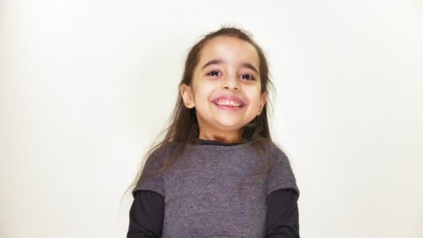 Little cute caucasian girl looks at the camera, smiling and then makes a sad face, white background 50 fps