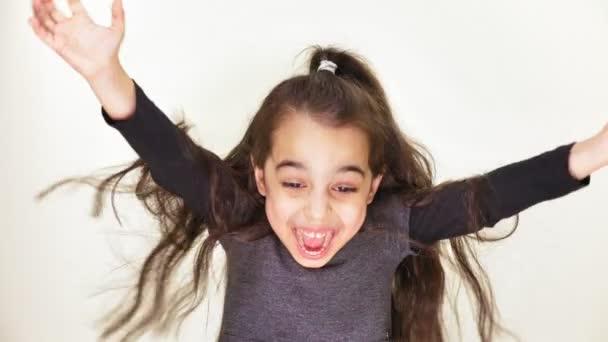 kleines schönes süßes Mädchen ist glücklich, lächelt, jubelt, hebt die Arme nach oben, überrascht, weißer Hintergrund, weißer Hintergrund 50 fps