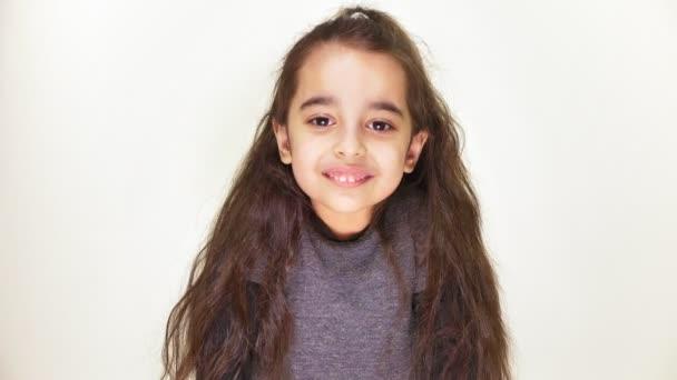 kleines glückliches Mädchen lächelnd und in die Kamera blickend, Porträt, weißer Hintergrund 50 fps