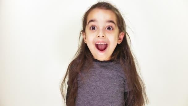 kleine niedliche kaukasische Mädchen, lächelnd, zeigt ein Gefühl der Überraschung, weit geöffneten Mund, Porträt weißer Hintergrund 50 fps