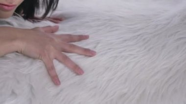 Female hand glides over a fluffy blanket, close-up 50 fps