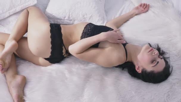 Fiatal szexi lány fekete fehérnemű fekszik egy, mosolygó, fehér hálószoba, nappali, kísértés koncepció, zár-megjelöl 50 fps