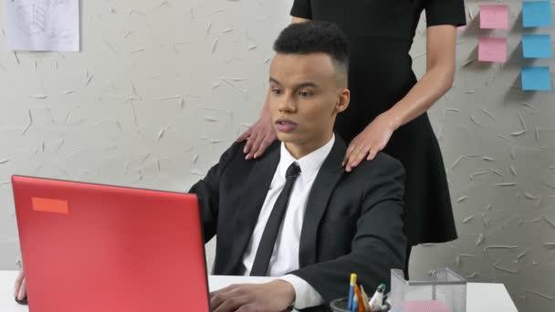 Mladý šéf flirtuje s mladé africké zmatená zaměstnance, jemně dotkne jeho ramena, masáže, obtěžování koncept, pracovat v kanceláři, Detailní záběr 50 fps