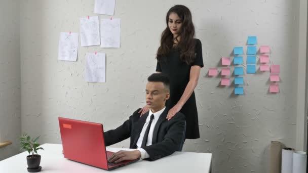 Mladý šéf flirtuje s mladé africké usmívající se zaměstnancem, jemně dotkne jeho ramena, masáže, obtěžování koncept, práce v kanceláři 50 fps