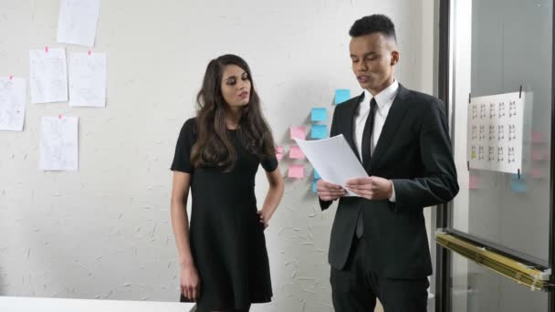 Young woman boss slaps a young guy on the buttocks, while he reads a report at the office, flirts, harassment concept 50 fps
