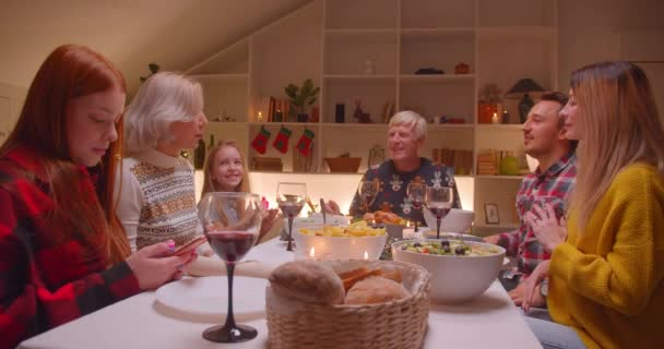 Big family Christmas dinner sing an evening song different generations