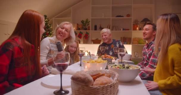 Big family singing song Christmas dinner evening grandparents children wine reunion dance