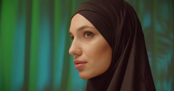 Caucasian girl black hijab neon make-up portrait light night green background