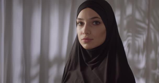 Caucasian girl black hijab neon make-up portrait light night white background
